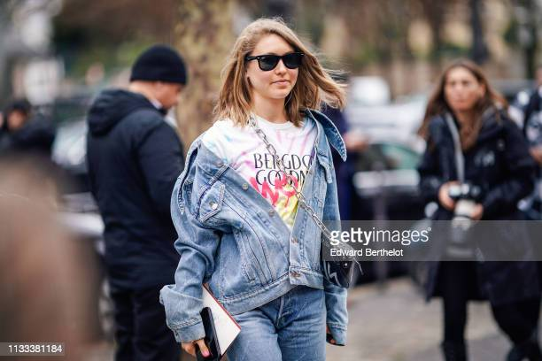 A guest wears sunglasses a blue denim jacket blue Balenciaga jeans a black bag outside Altuzarra during Paris Fashion Week Womenswear Fall/Winter...