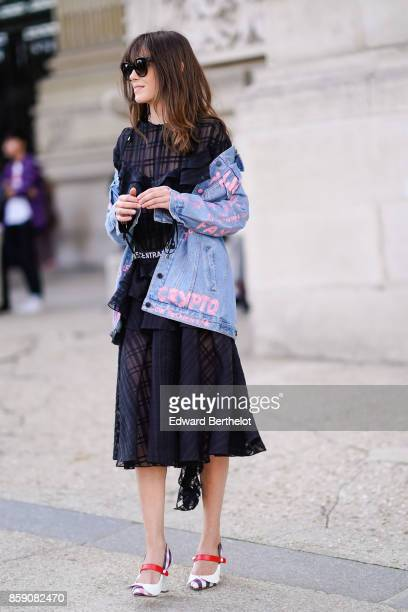 A guest wears sunglasses a blue denim jacket with pink flowers a black lace mesh dress white shoes with a red feature outside Elie Saab during Paris...