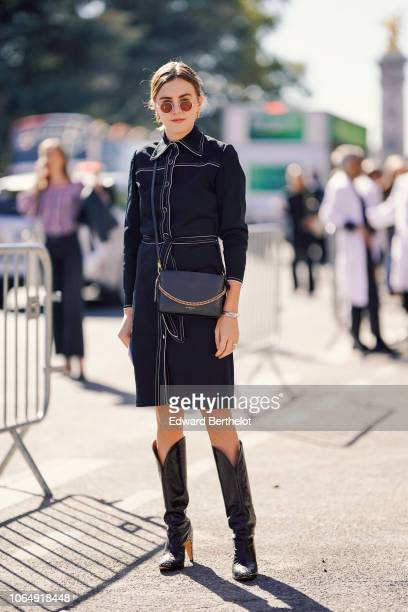 A guest wears sunglasses a blue denim shirt dress a bag black leather high boots outside Margiela during Paris Fashion Week Womenswear Spring/Summer...