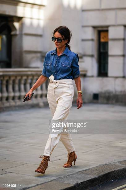 Guest wears sunglasses, a blue denim shirt, white pants, brown shoes, during London Fashion Week September 2019 on September 15, 2019 in London,...