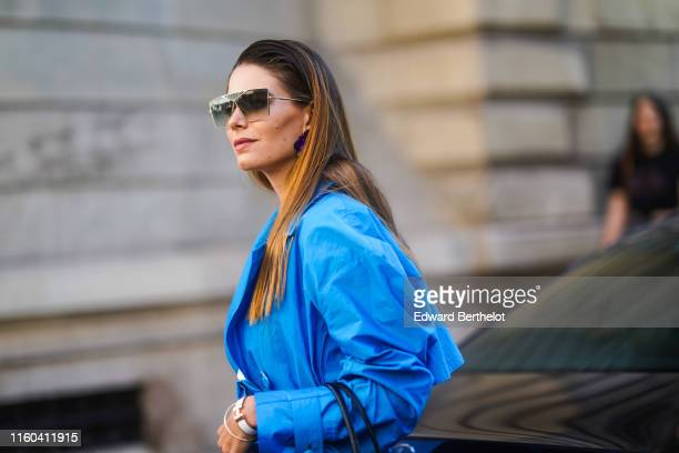 A guest wears sunglasses a blue dress outside Valentino during Paris Fashion Week Haute Couture Fall/Winter 2019/2020 on July 03 2019 in Paris France