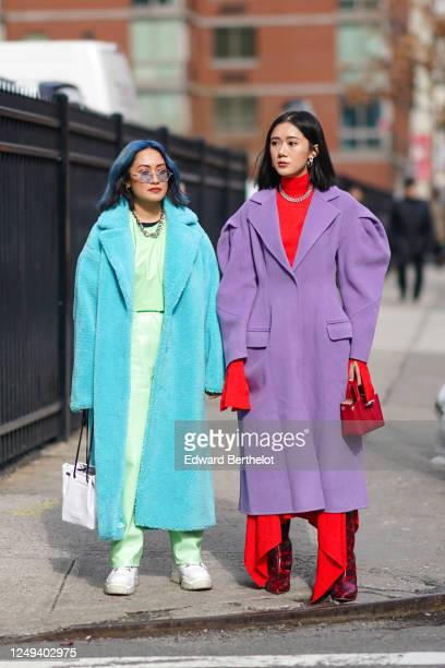Guest wears sunglasses, a blue fluffy long winter coat, a pale green pvc outfit, white sneakers, a bag ; a guest wears a red turtleneck pullover, a...