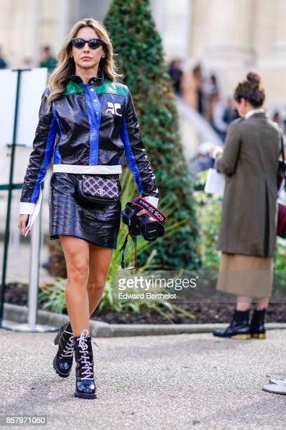 A guest wears sunglasses a blue green black leather jacket a chanel bag a black leather skirt black shoes with white shoe lace holds a canon 5d mark...