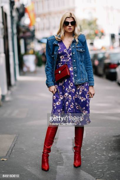 A guest wears sunglasses a blue jacket a purple flower print dress a red bag red thigh high leather boots outside Topshop during London Fashion Week...