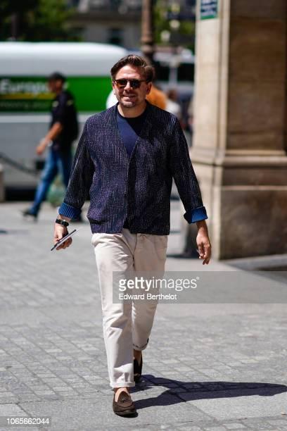A guest wears sunglasses a blue jacket white pants shoes outside Louis Vuitton during Paris Fashion Week Menswear SpringSummer 2019 on June 21 2018...