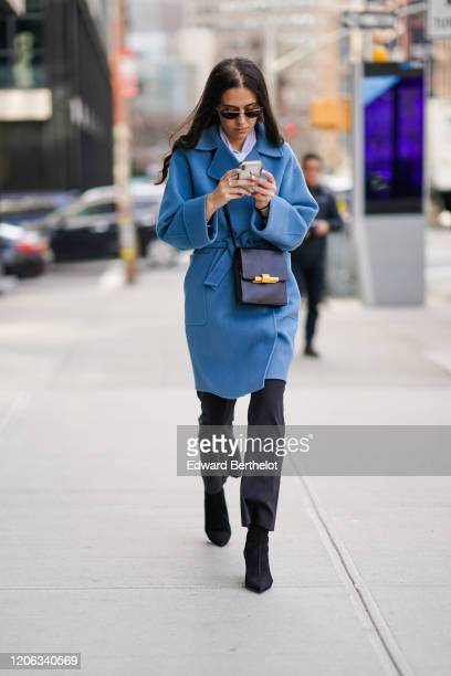 A guest wears sunglasses a blue long coat a bag black pants pointy shoes during New York Fashion Week Fall Winter 2020 on February 12 2020 in New...