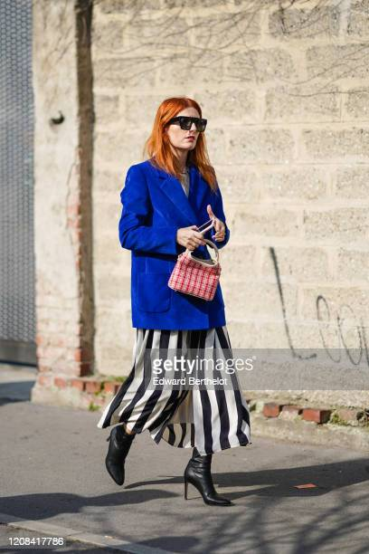 Guest wears sunglasses, a blue oversized jacket, a red checked bag, black and white striped skirt, black leather pointy high heeled boots, outside...