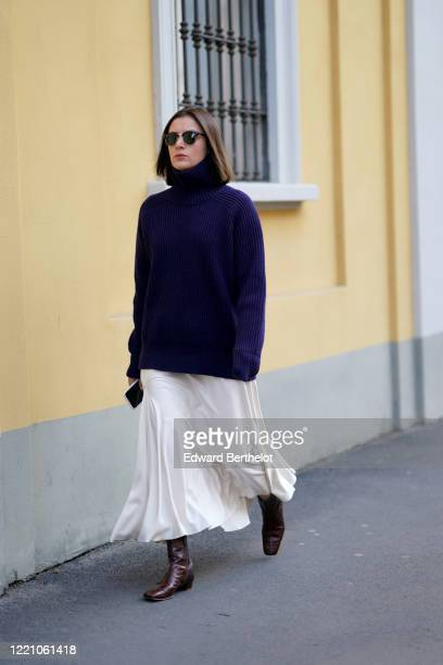 A guest wears sunglasses a blue oversized pullover a white skirt brown leather boots outside Tod's during Milan Fashion Week Fall/Winter 20202021 on...