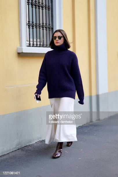 Guest wears sunglasses, a blue oversized pullover, a white skirt, brown leather boots, outside Tod's, during Milan Fashion Week Fall/Winter 2020-2021...