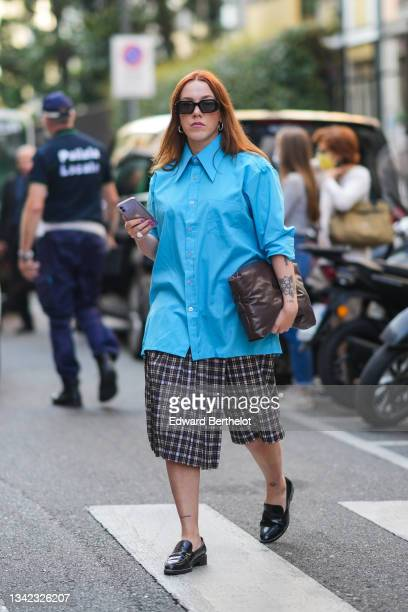 Guest wears sunglasses, a blue oversized shirt, black and white checkered large shorts, a brown shiny leather handbag, a white ring, black shiny...