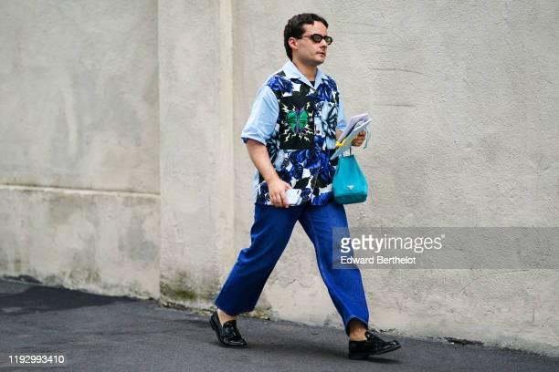 Guest wears sunglasses, a blue Prada shirt with floral print, a blue Prada bag, blue denim pants, black moccasins, outside the Prada show during...