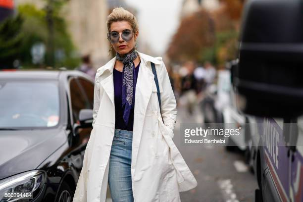 A guest wears sunglasses a blue print scarf a navy blue top a white trenchcoat blue jeans outside Lanvin during Paris Fashion Week Womenswear...