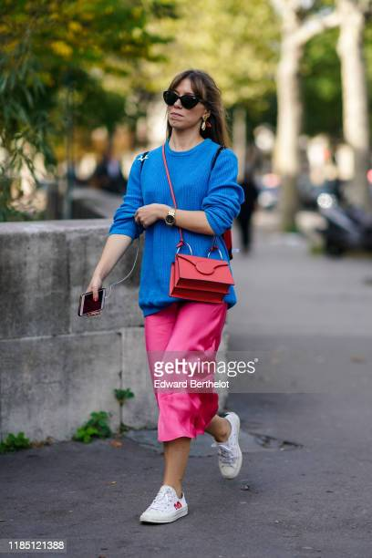 A guest wears sunglasses a blue pullover a red bag a pink lustrous skirt white sneakers during Paris Fashion Week Womenswear Spring Summer 2020 on...
