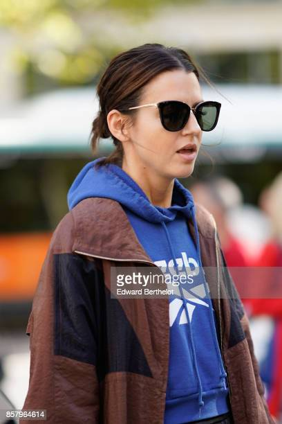 A guest wears sunglasses a blue Reebok hoodie a brown jacket outside Miu Miu during Paris Fashion Week Womenswear Spring/Summer 2018 on October 3...