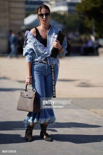 A guest wears sunglasses a blue ruffle denim jacket blue ruffle pants jeans a Hermes bag a 'Girl Gang' belt outside Nina Ricci during Paris Fashion...