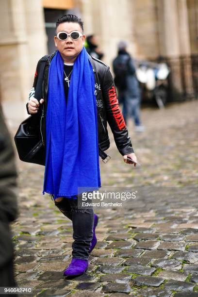 A guest wears sunglasses a blue scarf a black leather jacket with red prints on the sleeves ripped black jeans purple shoes outside Thom Browne...