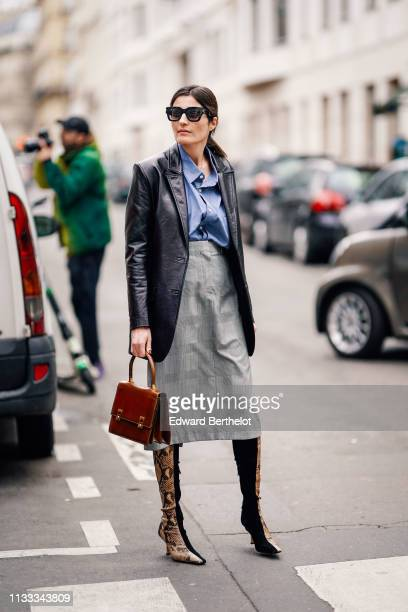 Guest wears sunglasses, a blue shirt, a black leather jacket, a brown handbag, a grey Prince of Wales check skirt, camel python pattern pointy...