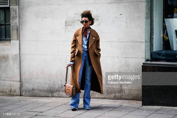 A guest wears sunglasses a blue shirt a fawn color coat with a large belt a fawn color bag with the Mona impression blue flare jeans during London...