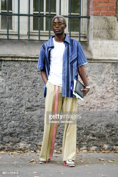 A guest wears sunglasses a blue shirt a white top flared wool pants outside the Paul Smith show during Paris Fashion Week Menswear Spring/Summer 2018...