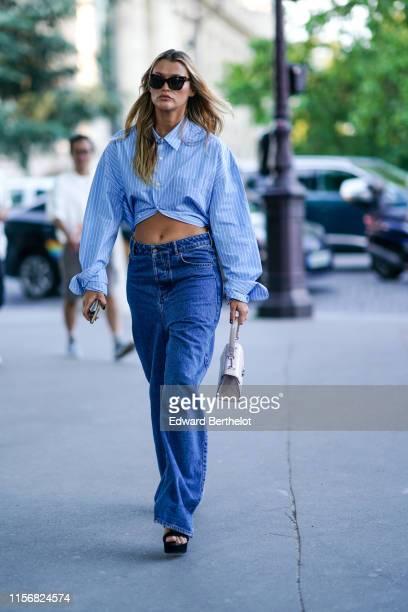 A guest wears sunglasses a blue shirt with white thin stripes lowwaist blue denim widelegs pants a white alligator pattern handbag black platform...