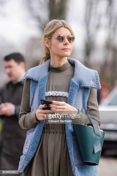 A guest wears sunglasses a blue sleeveless jacket a khaki dress a green bag outside Beautiful People during Paris Fashion Week Womenswear Fall/Winter...