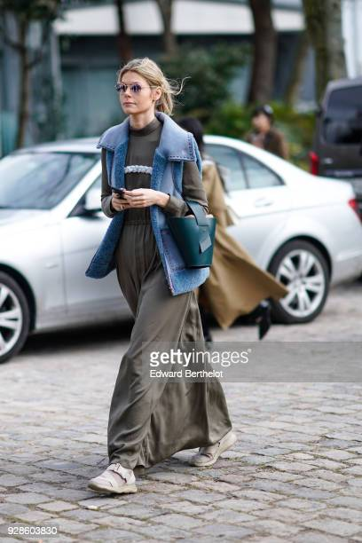 A guest wears sunglasses a blue sleeveless jacket a khaki dress a green bag outside Beautiful People during Paris Fashion Week Womenswear Fall/Winter...