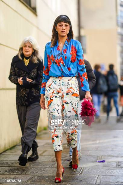 Guest wears sunglasses, a blue top with red floral print, crop pants, pointy shoes, a purple fluffy bag, during Paris Fashion Week - Womenswear...
