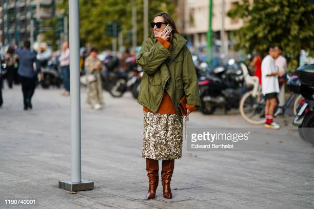 A guest wears sunglasses a brown alligator pattern bag a khaki jacket a rustcolor sweater a glittering sequined goldtone skirt brown pointy heeled...