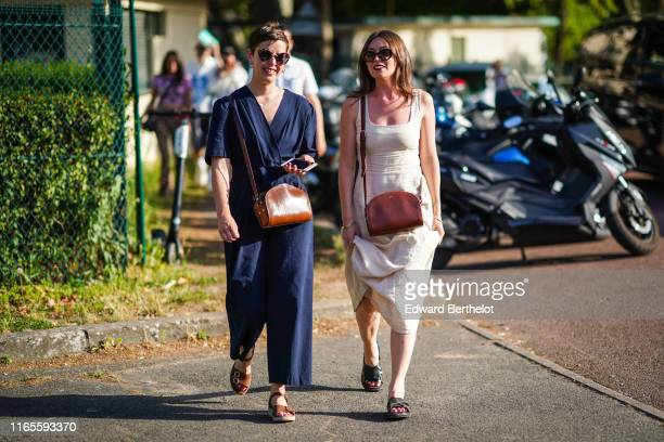 A guest wears sunglasses a brown bag a beige dress with a square neckline black sandals A guest wears sunglasses earrings a brown bag a navy blue...