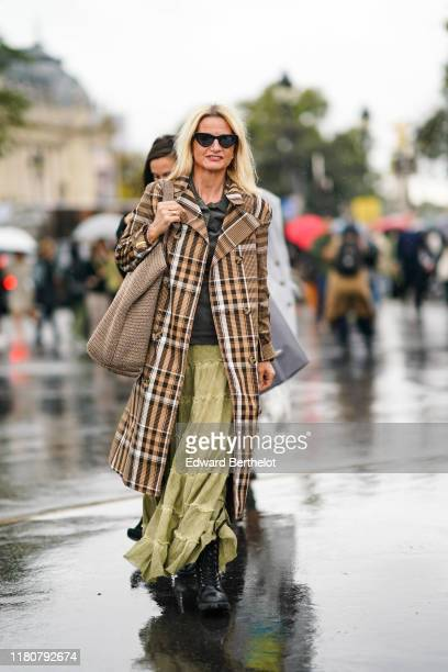 A guest wears sunglasses a brown checked pattern long coat a khaki green skirt a large wool bag a black shirt black shoes outside Chanel during Paris...