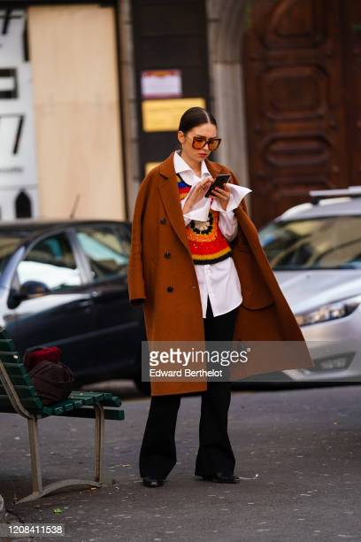 Guest wears sunglasses, a brown coat, a white long shirt, a multicolor pullover with printed patterns,, flared pants, during Milan Fashion Week...