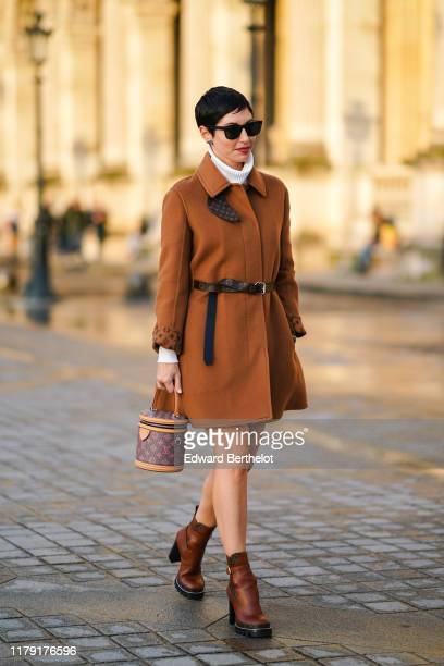 Guest wears sunglasses, a brown coat with printed vuitton logos, a white turtleneck pullover, a Vuitton belt, brown leather shoes, a Vuitton bag...