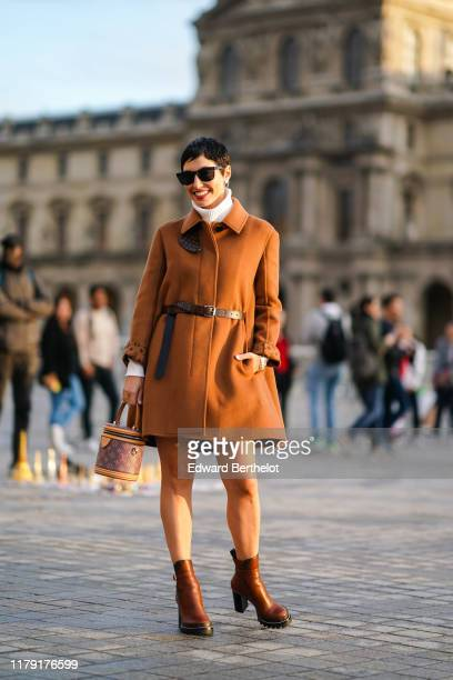 A guest wears sunglasses a brown coat with printed vuitton logos a white turtleneck pullover a Vuitton belt brown leather shoes a Vuitton bag shaped...