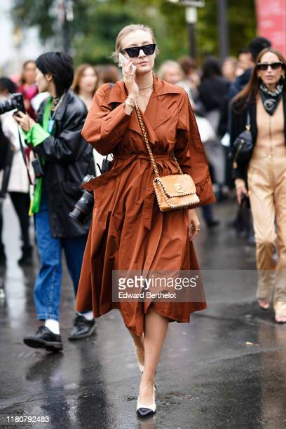 Guest wears sunglasses, a brown dress, a bag from Chanel, Chanel shoes, outside Chanel, during Paris Fashion Week - Womenswear Spring Summer 2020, on...