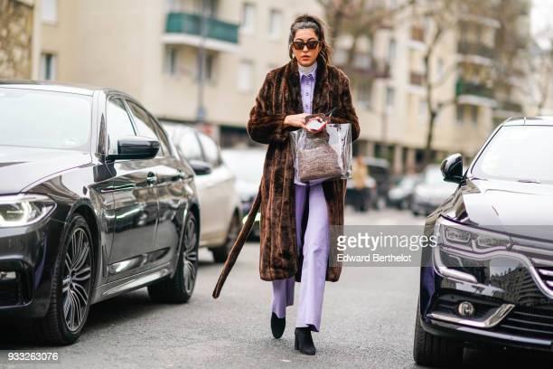 A guest wears sunglasses a brown fur coat a pale purple wideleg pants pantsuit a taupe handbag black boots during Paris Fashion Week Womenswear...