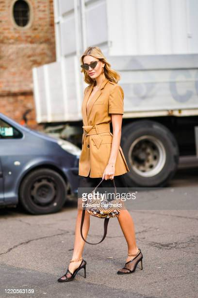 Guest wears sunglasses, a brown jacket, a belt, a black skirt, mesh pointy shoes, a Fendi bag, outside Max Mara, during Milan Fashion Week...