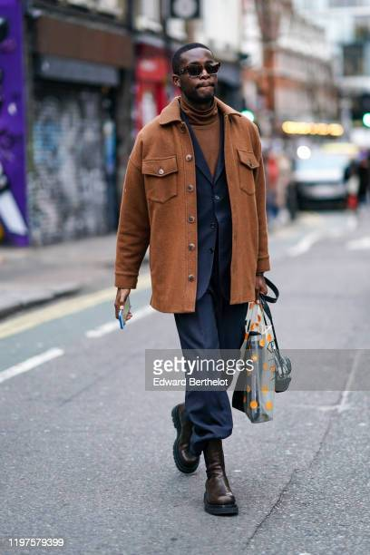A guest wears sunglasses a brown jacket a brown turtleneck pullover a navy blue blazer jacket blue pants brown leather boots a shopping bag during...