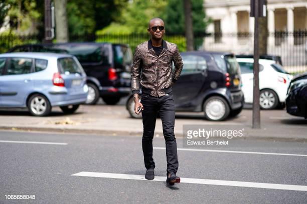 A guest wears sunglasses a brown jacket black denim pants outside Rick Owens during Paris Fashion Week Menswear SpringSummer 2019 on June 21 2018 in...