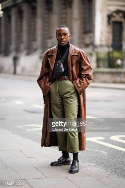 A guest wears sunglasses a brown leather coat a shoulder strapped bag green pants a belt black shoes a black turtleneck top during London Fashion...