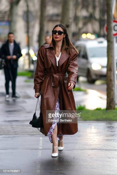 Guest wears sunglasses, a brown leather long trench coat with crocodile pattern, a floral print dress, a bag, white shoes, outside Alessandra Rich,...