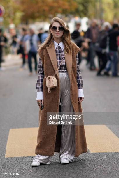 A guest wears sunglasses a brown sleeveless coat a checkered shirt with white collar shiny pants white sneakers outside Issey Miyake during Paris...