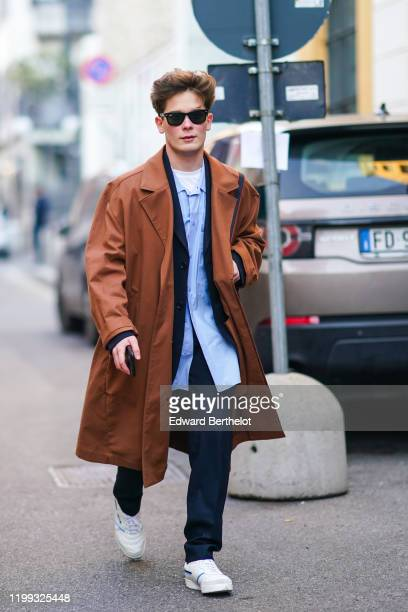A guest wears sunglasses a brown trench coat a blue shirt navy blue pants white sneakers outside Spyder during Milan Fashion Week Menswear...