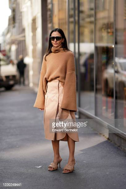 Guest wears sunglasses, a brown turtleneck oversized wool pullover with flared sleeves, a skirt, a Prada bag, salmon-colored padded leather sandals,...