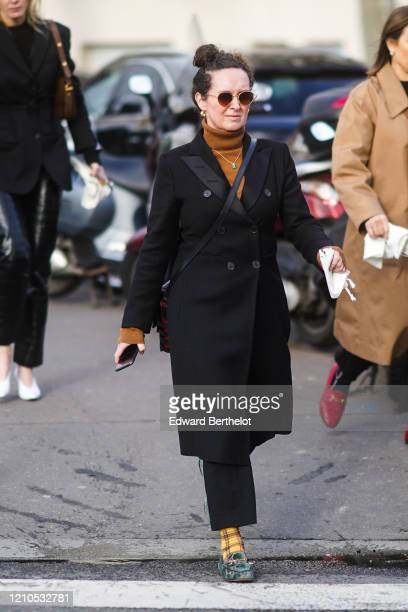 Guest wears sunglasses, a brown turtleneck pullover, a black coat, black pants, checked socks, shoes, earrings, outside Lacoste, during Paris Fashion...