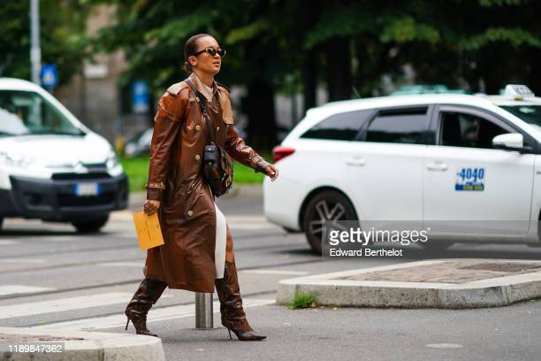 A guest wears sunglasses a brown vinyl trench coat a brown suede and black bag brown and black python pattern pointy heeled boots outside the Fendi...