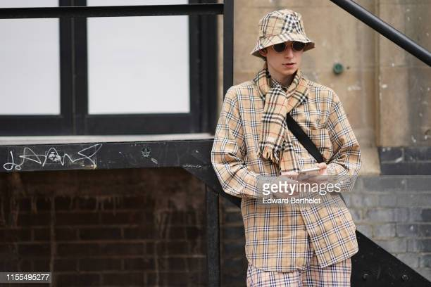 A guest wears sunglasses a Burberry check bob a Burberry check scarf a Burberry check shirt Burberry check pants during London Fashion Week Men's...