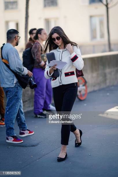 A guest wears sunglasses a burgundy Chanel bag a white tweed jacket black crop pants black flat shoes a grey bag outside Dries Van Noten during Paris...