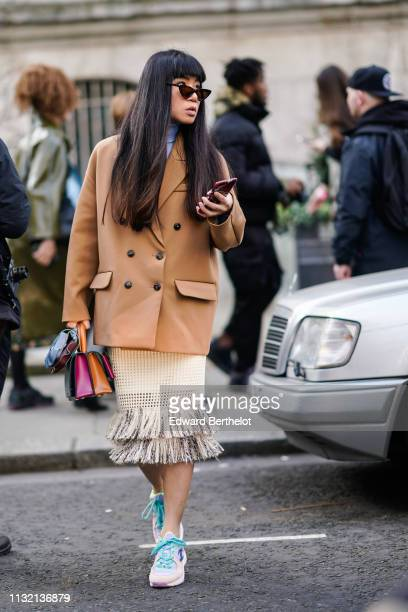 Guest wears sunglasses, a camel double-breasted jacket, a beige openwork fringe skirt, colorful Chanel sneakers, a purple and orange handbag , during...