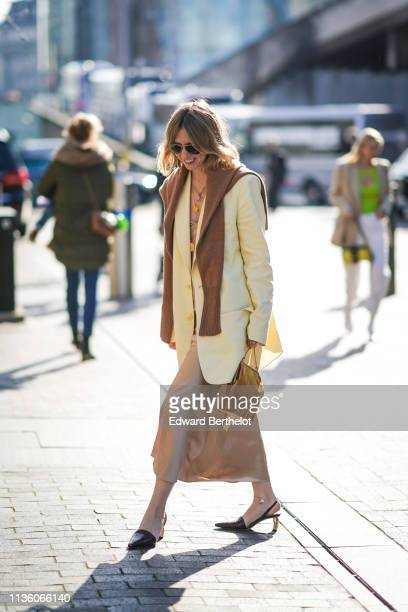 Guest wears sunglasses, a camel sweater, a pale yellow oversize coat, pale pink flowing skirt, a tan color bag, brown slingback pumps, during London...