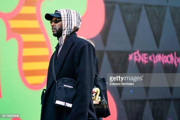 A guest wears sunglasses a cap a hood a black coat a 'minus two' bag during London Fashion Week Men's January 2018 at on January 6 2018 in London...
